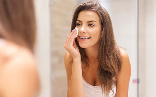 Молодая девушка очищает кожу лица