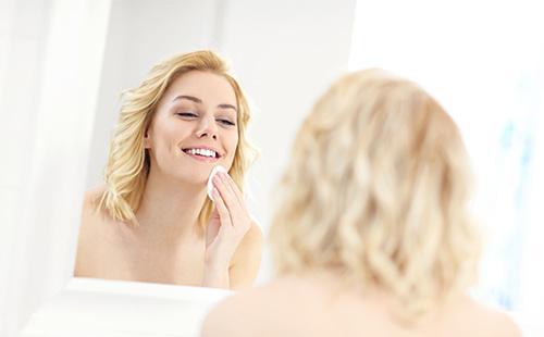 Женщина вытирает ватным диском лицо