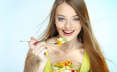 Девушка ест фруктовый салат