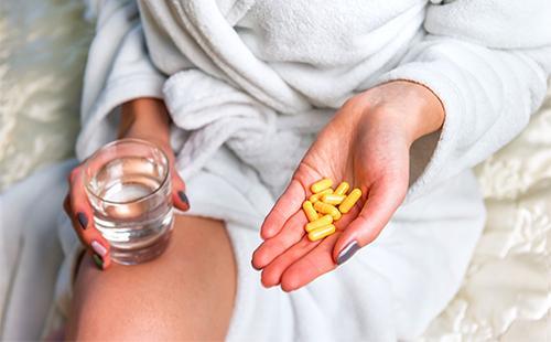 Девушка держит в руке желтые капсулы с лекарством