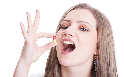 Девушка собирается принять таблетку