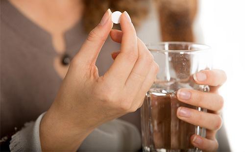 Женщина собирается выпить таблетку