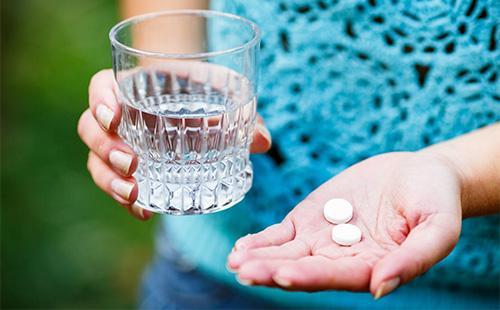 Две белые таблетки на ладони