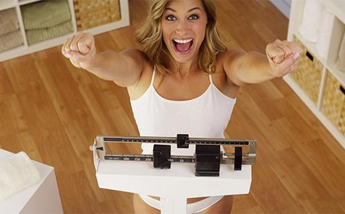 Девушка радуется на весах