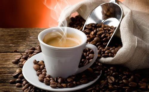 Чашка с кофе на фоне рассыпанного мешка кофейных зерен