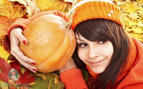 Девушка в оранжевой шапочке обнимает плоды осени