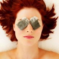 Рыжеволосая женщина с чайными пакетиками на глазах