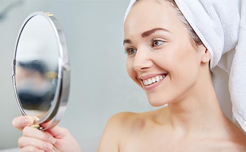 Молодая девушка смотрит на себя в зеркало