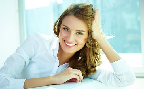 Красивая девушка в белой блузке оперлась на руку
