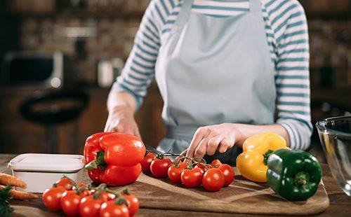 Женщина режет помидоры и перец на салат