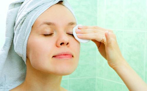 Девушка снимает макияж ватным диском