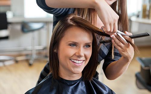 Женщине стригут волосы